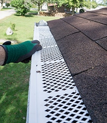 Contractor Checking Installation Of Plastic Leaf Guards