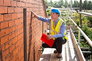 Roofing Inspector assesses brickwork on a gable end