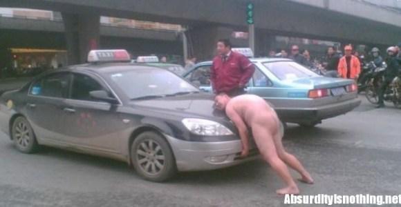Uomo nudo cerca di alzare un taxi in Cina