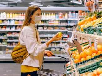 امرأة ترتدي قميصًا أصفر وسترة بيج تحمل حامل فواكه