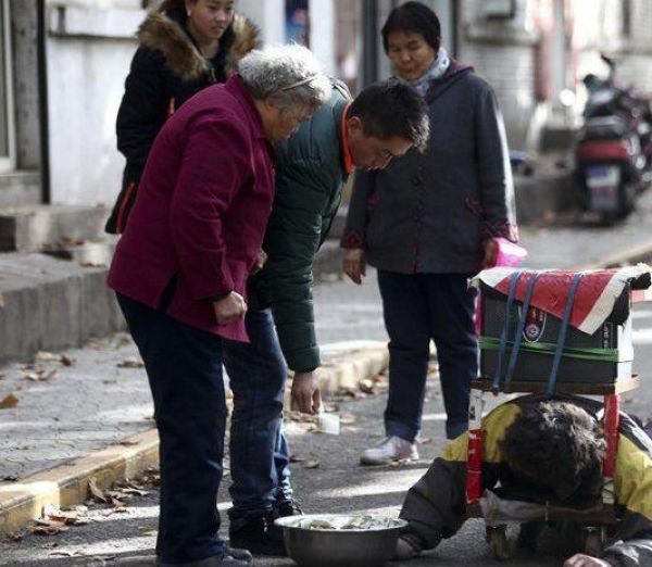 رجل صيني يتظاهر بالشلل ليكسب المال من المارة