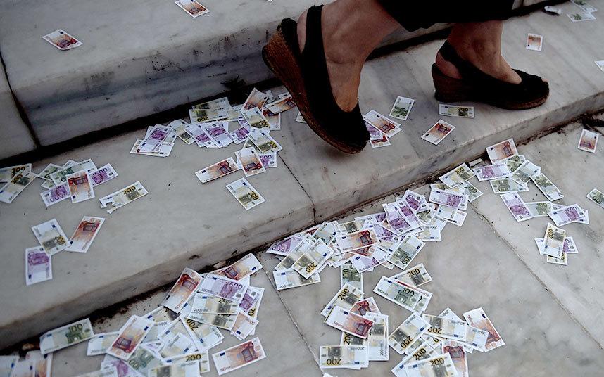 إلقاء عملة وهمية لليورو على الأرض أمام البرلمان اليوناني في أثينا خلال مظاهرة مؤيدة لأوروبا