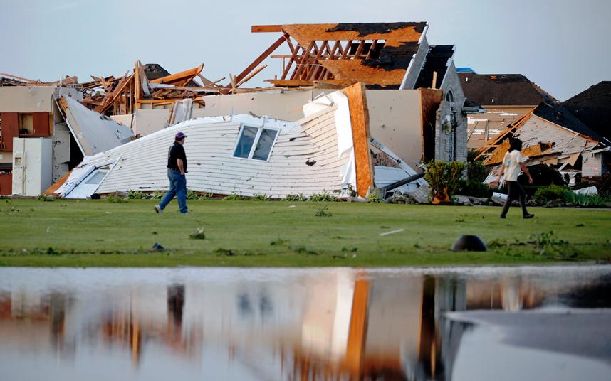 """الناس يتفقدون منازلهم بعد أن تحطمت بفعل أن ضرب إعصار مدنية """"كول"""" في ولاية إلينوي الأمريكية."""