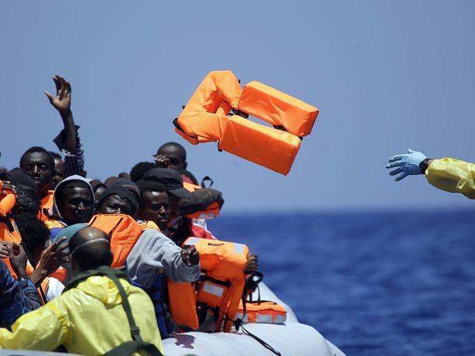 بحار من البحرية البلجيكية يقذف بسترات نجاة لقارب به مهاجرين