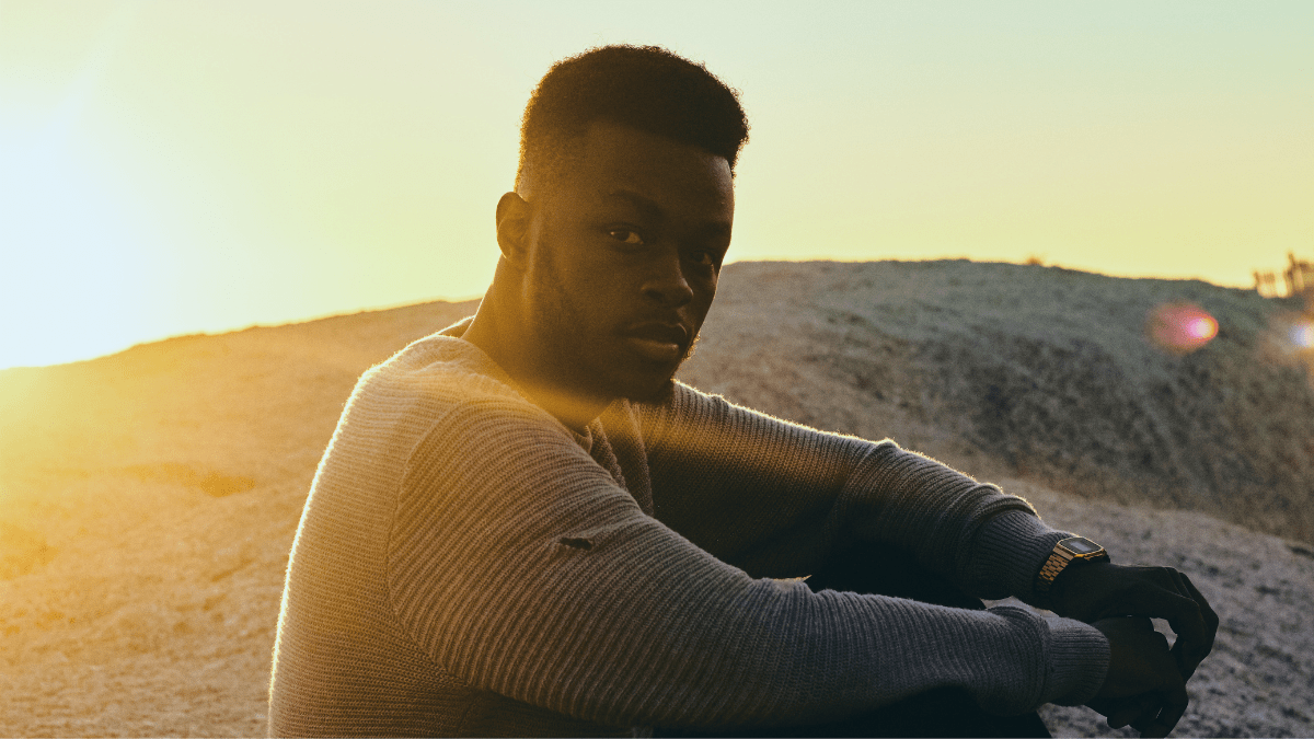 Young Black man looking out at sunset