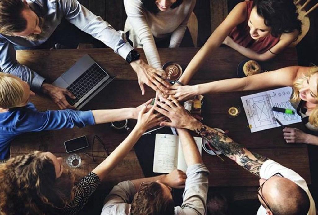 groupe de personnes avec les mains rassemblées au milieu d'une table