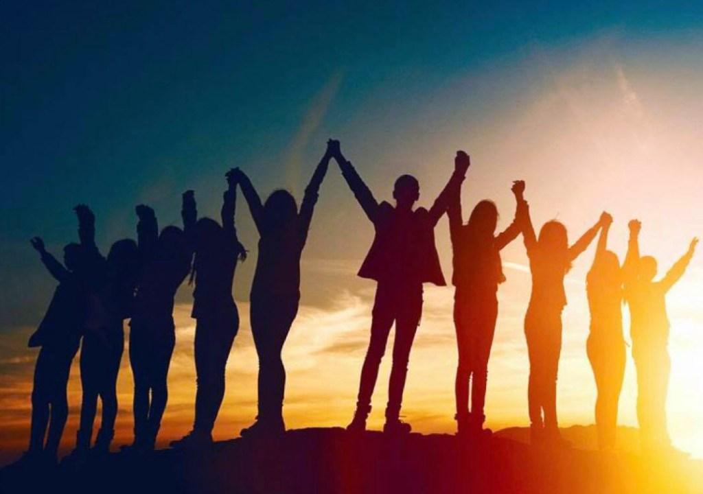 groupe de personnes se tenant les mains au dessus de la tête