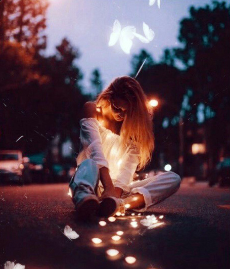 femme assise au milieu de la route avec des bougies