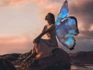 femme assise sur un rocher avec des ailes de papillon