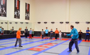 Coach Alexandr demonstrates fencing safety to new students