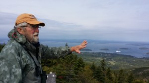 On Cadillac Mountain, Edwin W. Hawkes, a longtime volunteer at the bird watching program at Acadia National Park, gestures to show the flight of migrating raptors over Frenchman Bay.