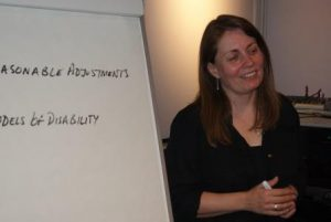 Image shows a picture of the trainer, Trish, standing in front of a flip chart