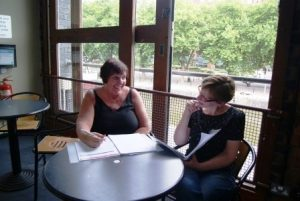 Image shows two workshop participants talking about a workbook exercise