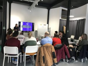 the photo shows a training room set up with participants seated around tables. Trish is standing at the front alongside a large screen TV which has the introduction slide from the training presentation on it