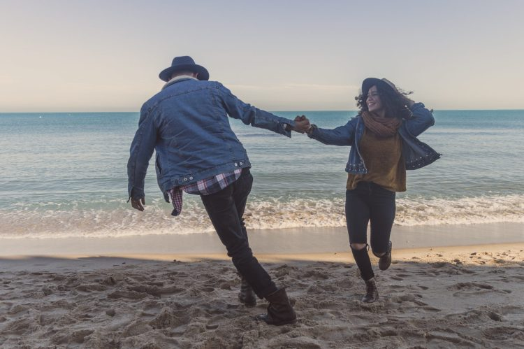 A couple walks together on the beach. They are feeling much happier since they have started neurodiverse couples counseling in Houston, Texas with Accessible Career.