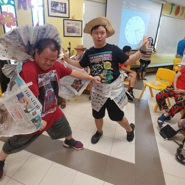 Two people posing in costumes made of newspaper