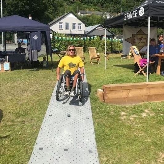 A man in a yellow shirt in a wheelchair uses Beach Trax across grass.