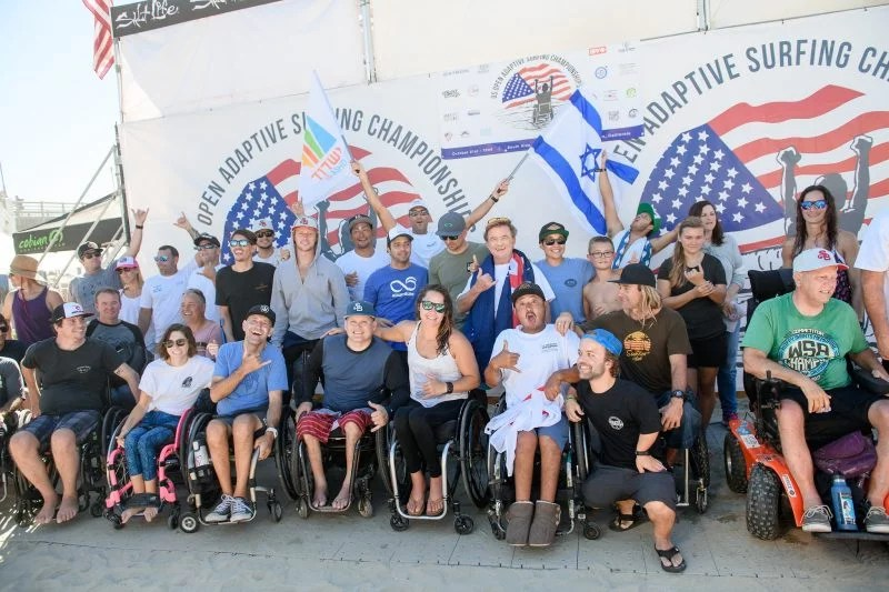 Image of adaptive surfers posing in front of the US Open banner during awards