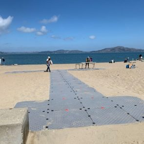Image showing a grey access pathway extending out from the boardwalk at the bay in San Francisco on a sunny day.