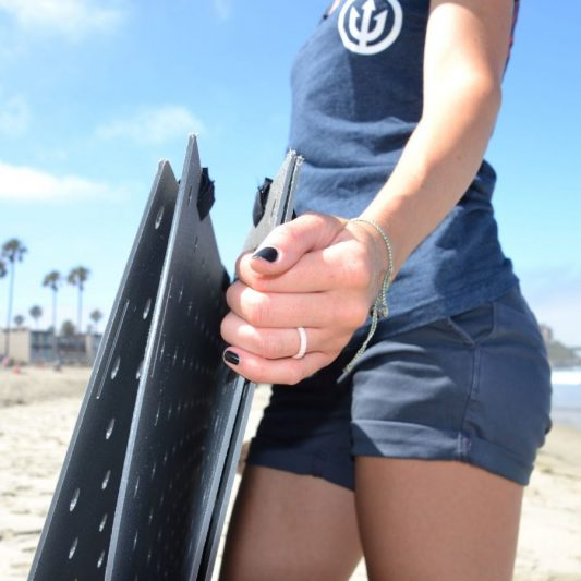 Image shows person grasping Beach Trax panels upright in a side view.