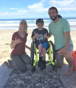 Kelly, wearing a red shirt, and Jeff, wearing a mint green shirt, kneel next to young adaptive surfer Hunter seated in his wheelchair on the Beach Trax.