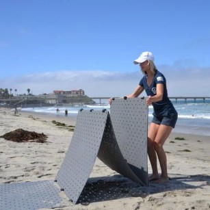 A blonde woman wearing shorts and a blue tshirt unfolds a grey access mat system called Access Trax over sand at the beach.