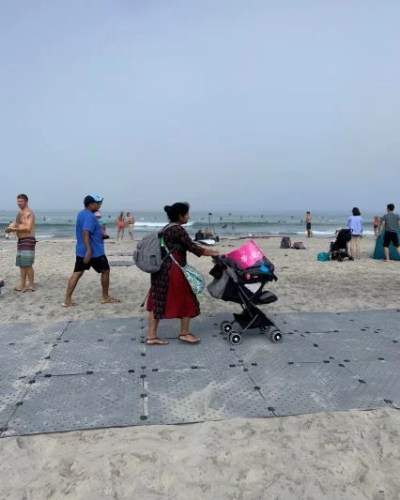 A women at the beach pushes a stroller atop Beach Trax.