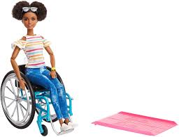 An African American Barbie wearing jeans and a striped shirt sits in her blue wheelchair next to a pink ramp.