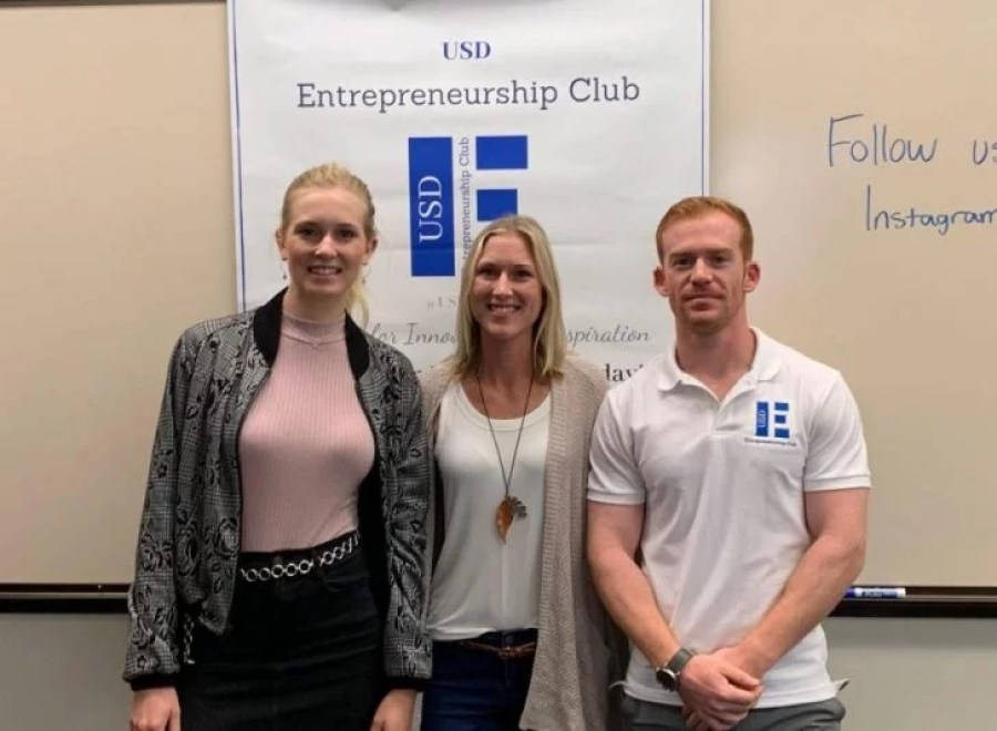 Access Trax CEO Kelly poses for a photo between 2 college students in front of the USD Entrepreneurship Club banner in a classroom.