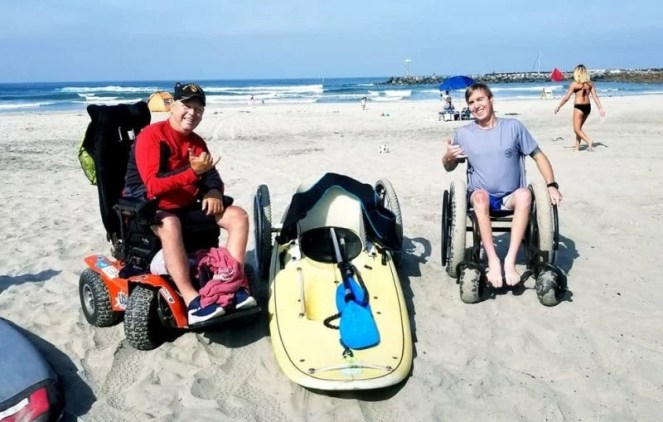 A man wearing a red rash guard sits in his power beach wheelchair and a man on the right sits in his manual beach chair with all-terrain tires at the beach. There is a waveski on the ground between them.