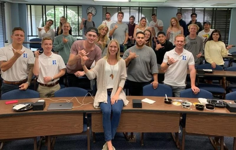 A blonde woman sits on a desk in front of the classroom smiling for a photo with about 25 college students in the background standing.
