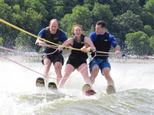Two male volunteers assist a smiling woman as the three stand to water ski on the lake.