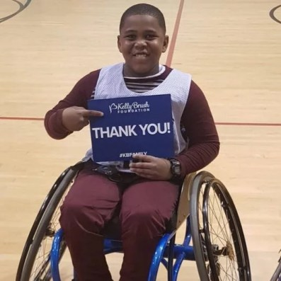 "An adolescent boy smiles while seated in his wheelchair on a basketball court. He is holding a sign that says ""Thank you"" to the Kelly Brush Foundation."