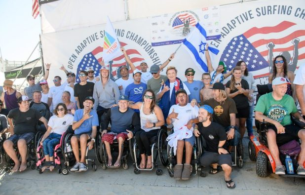 "A group of people with diverse abilities cheers for a picture in front of the banner ""US Open Adaptive Surfing Championships."""
