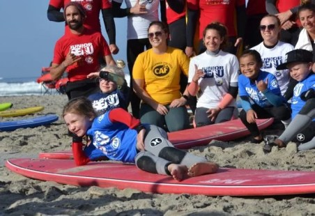Challenged Athletes Foundation volunteers and young participants wear red, yellow, blue, and white surf rash guards and pose for a photo on the sand with surf boards. A young girl with a prosthetic leg smiles in the front.