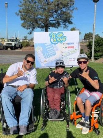 Beto, the Gurmilan Foundation founder, poses for a photo with two young grant recipients at his annual Walk and Roll Event. Beto is in his power chair and the two teenage boys are in their manual chairs in front of the Walk and Roll sign on grass.