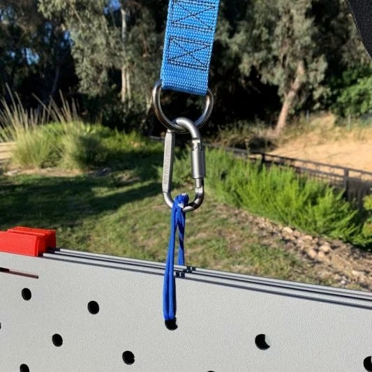 "Image shows blue paracord looped through a 1/2"" hole lined up across 5 pieces of stacked Access Trax mats. The other end of the paracord is connected to a carabiner which is connected to a metal D ring on the blue carrying strap mechanism. There is grass in the background."