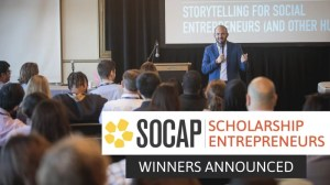 "Image shows a group of people seated looking at a speaker on the podium with a projector screen in the background. The speaker is a man wearing a blue suit. The text says ""SOCAP Scholarship Entrepreneur Winners Announced."""