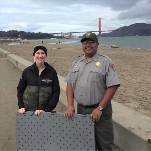 Image shows Access Trax CEO Kelly, a blonde woman wearing a black and camo zip up jacket, on the left smiling standing next to a National Park Accessibility Coordinator who is a taller man wearing a hat and tan button up with dark green cargo pants. They are both holding a stack of Access Trax panels in front of them and the Golden Gate Bridge is in the background.
