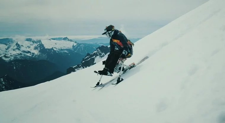 Image shows a woman wearing snow gear and a helmet skiing down a snowy mountain using her monoski.