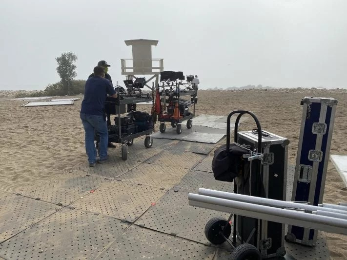 Image shows a large platform made up of interconnected squares (Access Trax) over sand near a lifeguard tower on a foggy day. There is various movie film equipment and two men standing near a dolly facing the lifeguard tower.