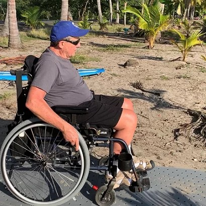 A man wearing a blue hat uses his wheelchair on a portable grey Access Trax pathway on the beach in Costa Rica.