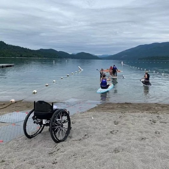 mage shows adaptive athletes paddling on a lake in Montana on a cloudy day. In the foreground is the sandy lake shore with grey Access Trax mats leading to the water. There is an empty manual wheelchair.