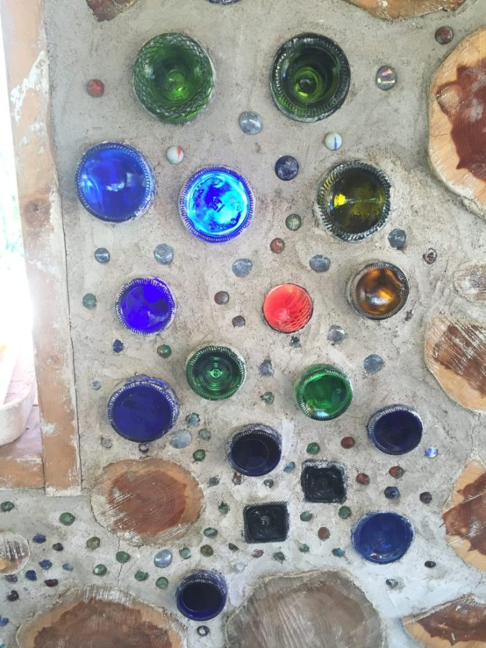 Using bottles in a cordwood wall is a beautiful way to reuse common materials while letting in light and color! #cordwood #bottlewall