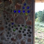 A little blue truck made out of bottles inside of a cordwood wall