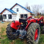 Massey Ferguson 50 in front of our cordwood house