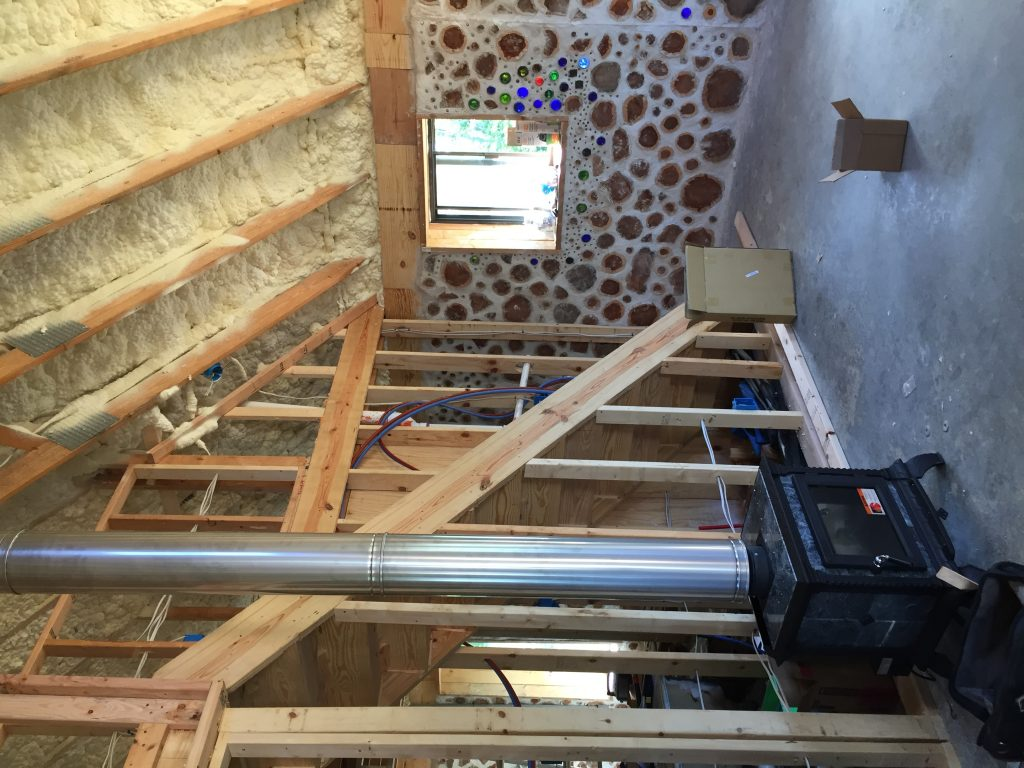 Soapstone stove in a cordwood house. Check out more of our off grid building project!