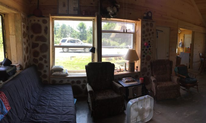 Inside the living room of our cordwood home. Its still a work in progress! Find out the answers to the most common questions we hear in this post #alternativebuilding #naturalbuilding #cordwoodmasonry