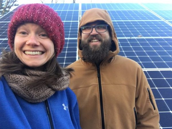 couple in front of solar panels