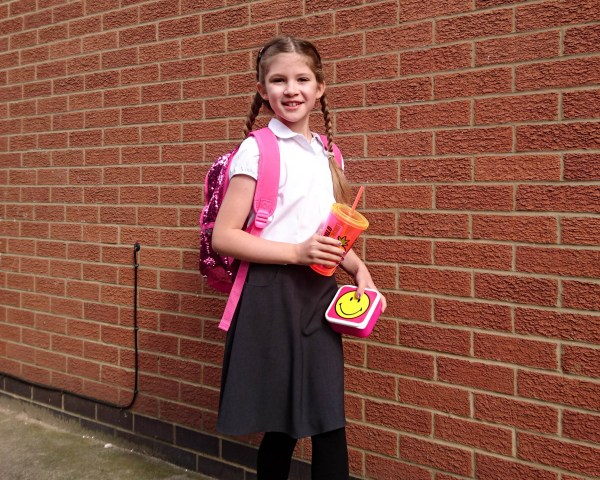 Back to school accessories for tweens Emma walking with cup in hand and bag on back